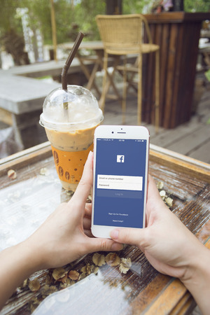 mark zuckerberg: prachuapkhirikhan,thaialnd-august 6,2016: woman hand holding a smartphone with Facebook page on screen,at coffee cafe,Facebook is very well know social networking service founded in 2004 by Mark Zuckerberg,socialism concept