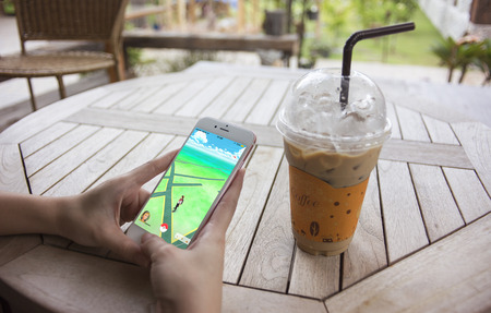 play popular: Prachuapkhirikhan,Thailand - August 6,2016 : woman hand holding smart phone to play Pokemon Go,popular virtual reality game for mobile devices,at coffee cafe table,first day opened in thailand