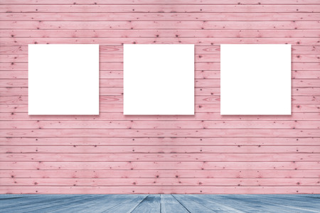 lit collection: room interior  vintage with Three canvas frame on pink pastel wooden wall for image advertising,blue wooden floor,Three empty frames in a room against a wooden wall Stock Photo