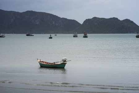 Traditional fishing  boat laying on a beach near the sea with big and long mountain in background,cloudy sky,filtered image,high contrast picture style Stock Photo
