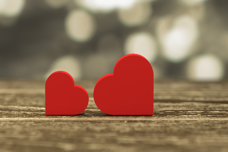 out of focus: 3D rendering - illustration of red heart box put on a wooden table with gold blurred abstract out of focus light in background,love couple concept
