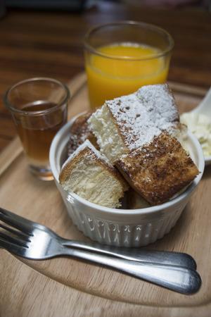cerrar una tostada en una taza con azúcar glas en polvo en la parte superior, miel en una taza y jugo de naranja en un vaso, poner en la placa de madera, mesa de madera, desayuno de la mañana, menú de tostadas de miel