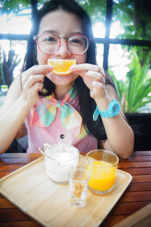 say cheese: portrait of happy asian woman in a cafe with mandlin orange against of a mouth like a smile,say cheese concept,happy with food concept,happy morning breakfast Stock Photo