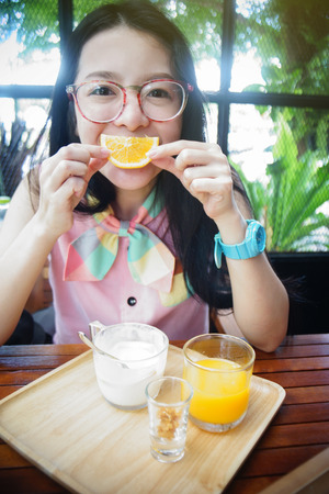 say cheese: portrait of happy asian woman in a cafe with orange fruits against of a mouth like a smile,say cheese concept,happy with food concept,happy morning breakfast