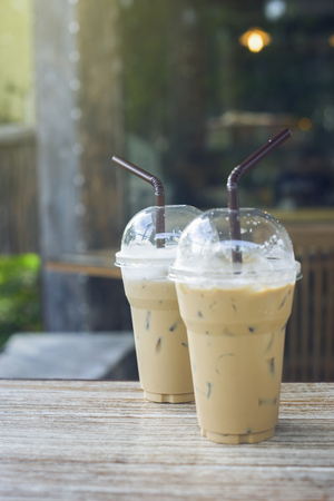 two of take away iced coffee cup put on a wooden table at coffee cafe. blurred background.selective focus