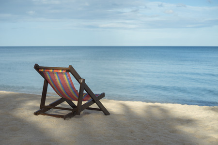 portrait of a beach chair on a white sand beach with bluesky and blue sea in background,selective focus,filtered image,rest moment,time to rest,perfect time Stock Photo