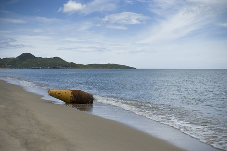 beach buoy: old metal buoy laying on a sand beach,blue sky and mountain in background Stock Photo