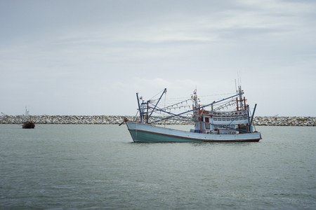 traditional fishing boat laying on the sea.cloudy sky.fitered image.selective focus