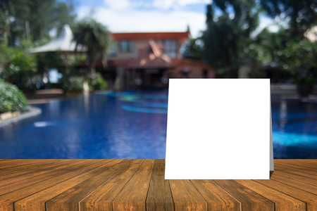 white card put on wood table and beautiful view of swiming pool at resort in background. product display template. Business presentation.clipping path include