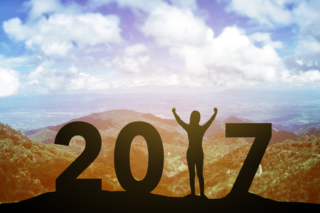 Silhouette young woman standing and raising up her hand about winner concept on at 2017 over a beautiful sunset or sunrise at the sea. background for happy new years. success in 2017 years