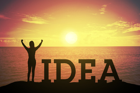 Silhouette young woman standing and raising up her hand about winner concept at IDEA text over a beautiful sunset or sunrise at the sea. background for success in 2017 years .hope to business success