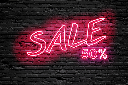 banner ads: SALE 50 % Percent. fluorescent Neon tube Sign on dark brick wall. Front view. Can be used for online banner ads or background. night moment.
