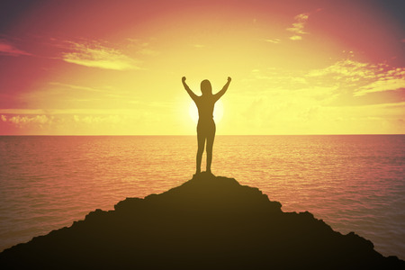silhouette of winning success woman at sunset or sunrise standing and raising up her hand in celebration of having reached mountain top summit goal.Happy celebrating.business success concept