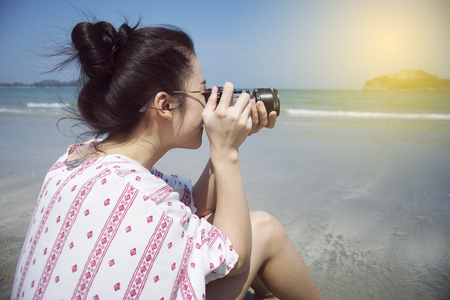 hua: Asian teenager woman has take a relaxing on beautiful beach. Wearing sunglasses and holding a camera. Siam Smiling girl. rest time at the beach with big mountain. Filtered image. Selective focus