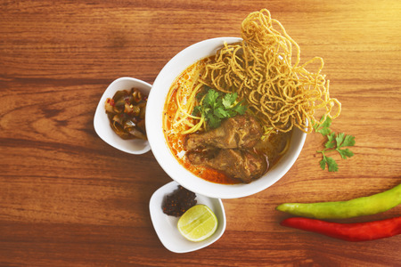 Top view food concept : Curried Noodle Soup (in thailand is called Khao soi) with two piece of chicken on top. spicy delicious thai noodle. famous Thai Food cuisine northern style. light effect added