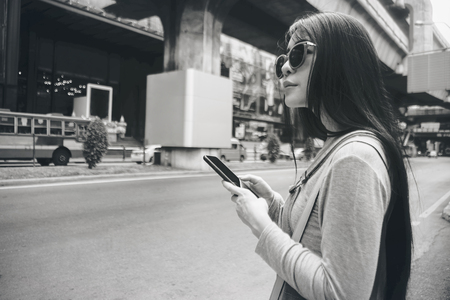 Beautiful young Asian girl using smart phone near street . female traveler find new place for travel concept. filtered image. standing near the street. Stockfoto