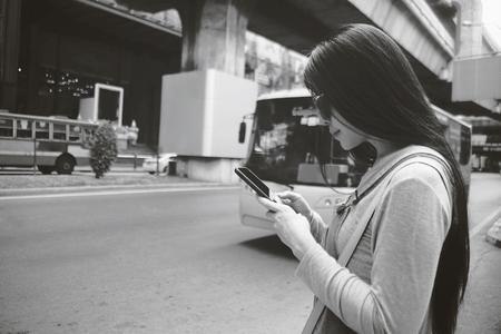 Beautiful young Asian girl using smart phone near a street . female traveler find new place for travel concept. filtered image. standing near the street.
