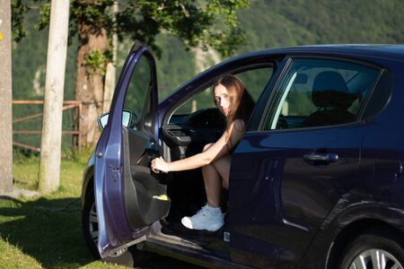 young girl getting into her new car on a sunny day