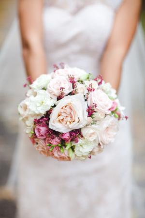 arm bouquet: Beautiful wedding bouquet in hands of the bride