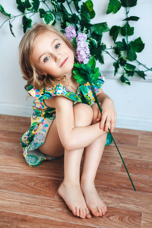 Little girl blonde sits on the floor with a flower in her hand in a room decorated with flowers Stock Photo