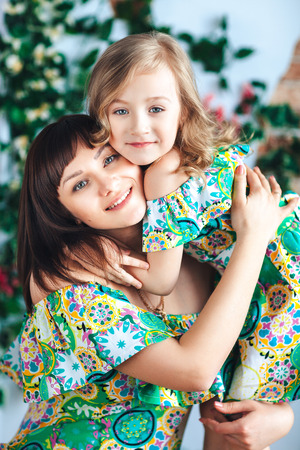 Close-up mother and daughter in a bright dress hugging and smiling