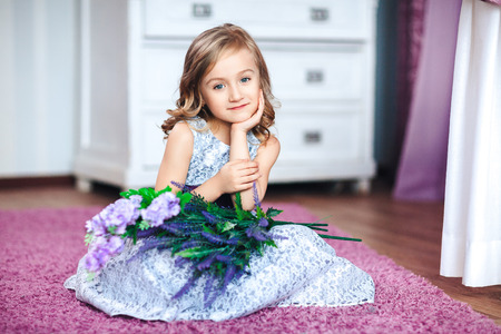 Little blonde girl in a beautiful dress sits on the floor with flowers on her knees Stock Photo