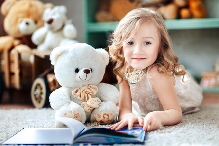 bedtime story: Little blonde girl is reading a book in a childrens room with a toy teddy bear