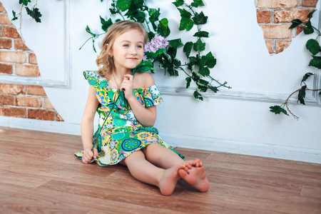 Little girl in a bright dress in a room decorated with flowers