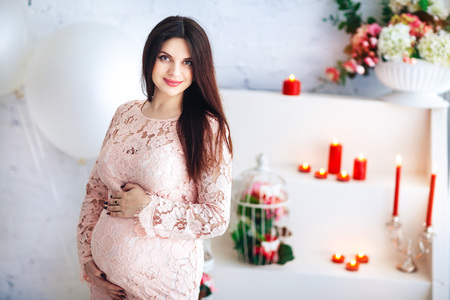 Young pregnant woman in pink dress on a light background Banco de Imagens