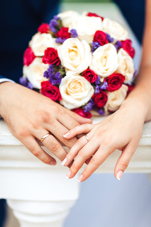 commit: Bride hands with ring and wedding bouquet
