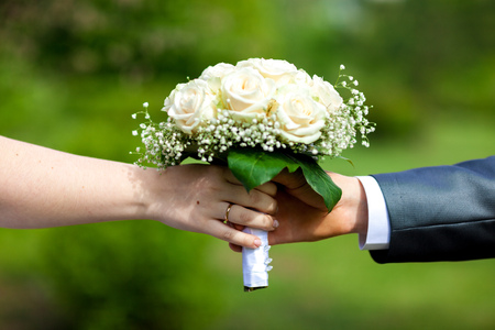The hands of the bride and groom hold a wedding bouquet Stock Photo