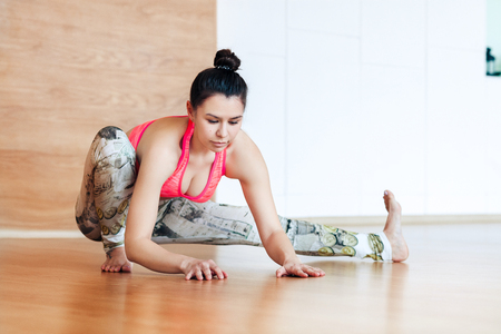 woman stretching and warming up before working out at a yoga Stock Photo