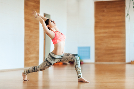 Young woman of sports appearance practicing yoga poses