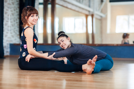 trainer helping women in leg stretching workout at gym fitness. Two smiling women warm up before training Stock Photo