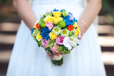 arm bouquet: The bride is holding a colored bouquet in her hands, close-up.