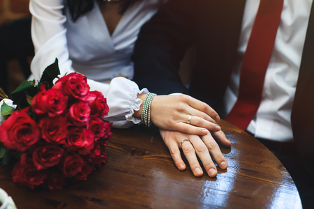 Bride hand with ring and wedding bouquet of red flowers Stock Photo - 78339132