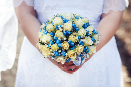 Beautiful wedding bouquet of tea roses with blue ribbons in the hands of the bride, top view horizontally