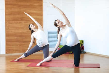 Two young pregnant fitness model in sportswear doing yoga, pilates training, Utthita Parsvakonasana, Extended Side Angle Pose