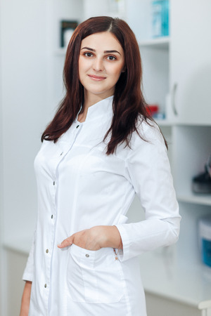 Portrait of female brunette cosmetologist in uniform in the cosmetology office