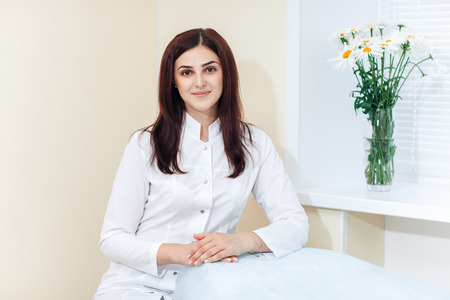 Portrait of female brunette cosmetologist in uniform near the window in the cosmetology office Standard-Bild