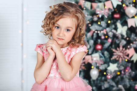 portrait of a little blonde girl with curls near a tree with brightly colored lanterns and flags. The concept of Christmas Stock Photo