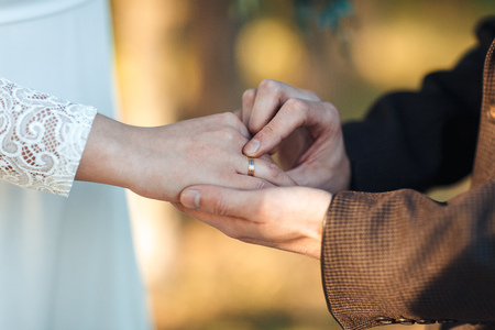 The hands of the newlyweds. A mans hand puts on a ring. wedding ceremony. Stock Photo