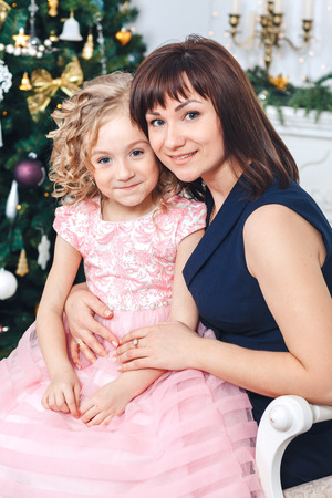 happy mother with her daughter sit near a white fireplace next to a tree