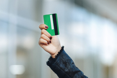 closeup of green credit card holded by woman hand.