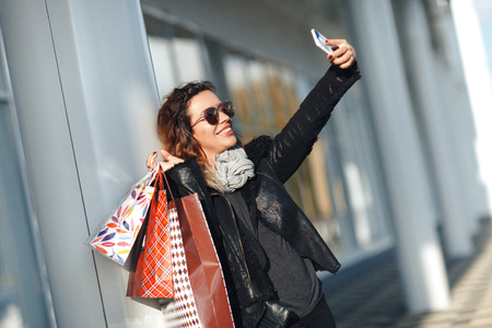 Woman in sun glasses a black leather jacket, black jeans Holding a Bunch of Shopping Bags Doing Selfie in front of mirrored windows on the Street