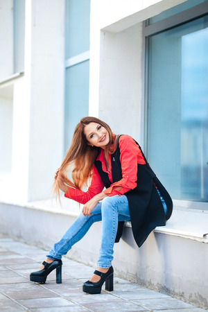 Portrait of young lady in a red shirt and a long sleeveless jacket sitting in front of mirrored shop windows, looking at camera. Female fashion concept. Outdoor