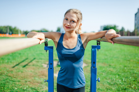 Beautiful young girl in a blue shirt and leggings on the uneven bars, on the outdoor sports ground in summer looking at camera and smiling