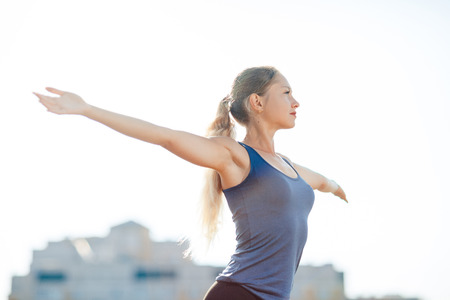 Young fitness woman in a blue shirt and leggings smile spread her hands to the sky for success in waiting the sun shines in her face, in stadium on the background of houses