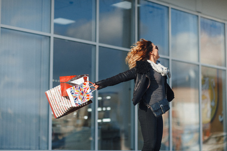 Lovely young woman in mirrored sunglasses, a black leather jacket, black jeans turns around holding shopping bags on window background Stock Photo