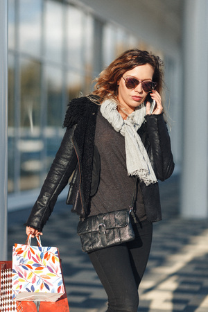 Woman in sun glasses a black leather jacket, black jeans with shopping bags talking on mobile phone in front of mirrored windows on the Street